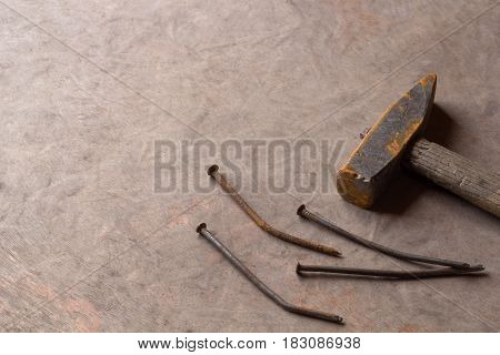 rusty old nails and hammer on wood background