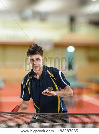 Portrait of young man playing table tennis in the competition