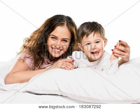 Cheerful woman with her cute little son having fun in bed on white background