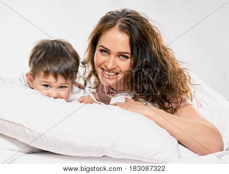 Cute smiling little boy embracing his happy mother