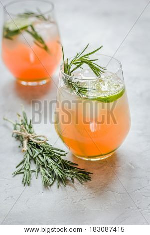 glass of fresh juice with lime and rosemary for healthy drink on stone kitchen table background