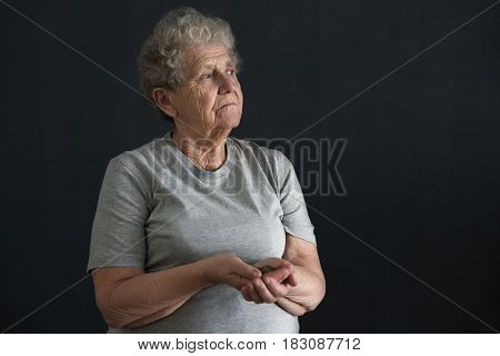 Senior woman with coins on dark background. Poverty concept