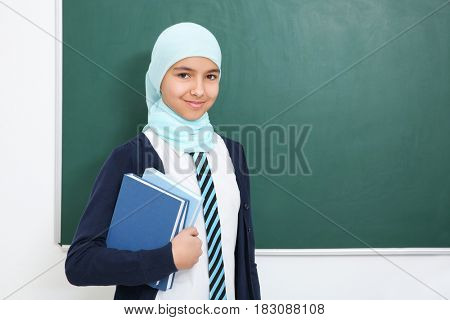 Cute girl with books standing near green school blackboard