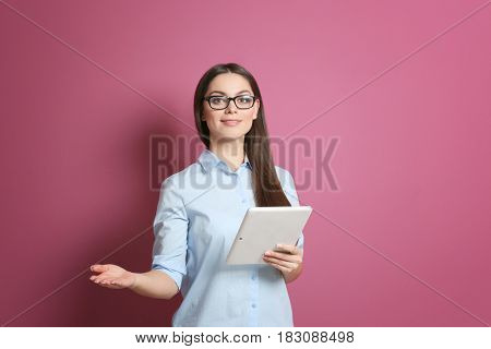 Young beautiful woman with tablet on color background