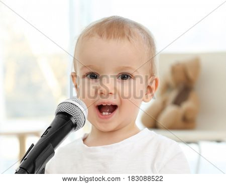 Cute baby with microphone at home