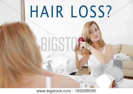 Hair loss concept. Young woman with brush in front of mirror