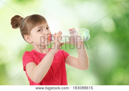 Little girl with bottle of clean water on blurred background