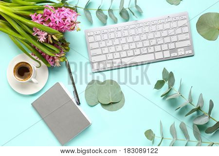 Keyboard and coffee with flowers on table, top view