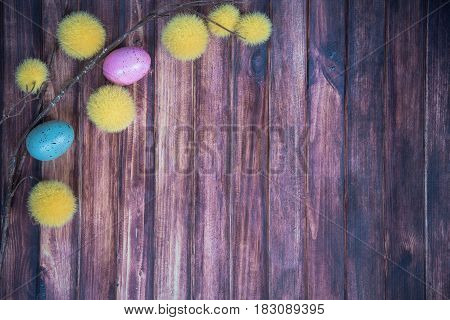 easter background with colored eggs yellow branches and copy space