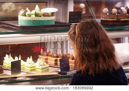 Little Girl In Confectionary Shop Looking At The Display. Sweet Treats Variety. Small Business And C