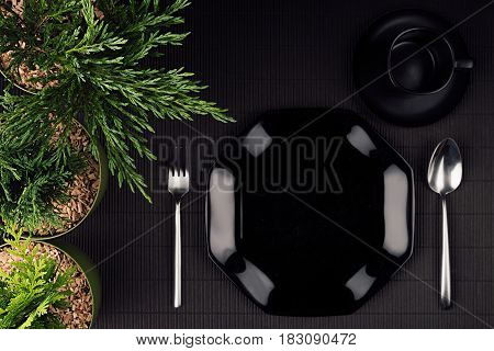 Eco dark modern minimalistic restaurant menu mock up with black glossy plate spoon fork green plants top view.