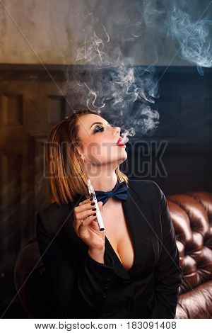 Young attractive girl in a jacket and bow tie smokes electronic cigarette. Femme fatale. Evening makeup smokey eye. Vape