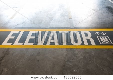 Elevator Sign Painted On The Cement Ground Of A Parking Area Space