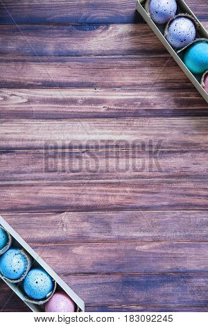 assorted colorful painted easter eggs in a gift box on wooden background with copy space