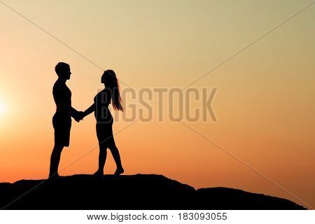Silhouette of attractive confident half naked man propose marriage to bikini woman for love valentine lover church marriage bound ring heart soul surrender dedication sun set orange sky concept