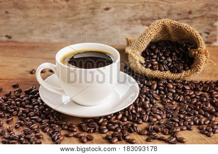 coffee cup and coffee bean in bag sack on wood background