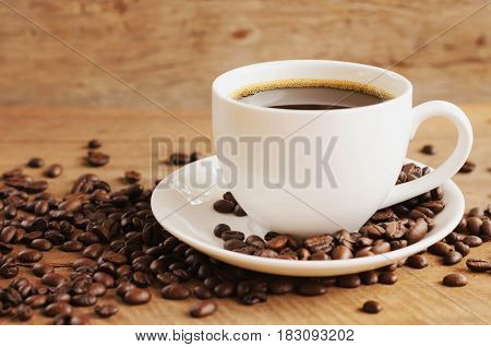 cup of coffee with beans on table background