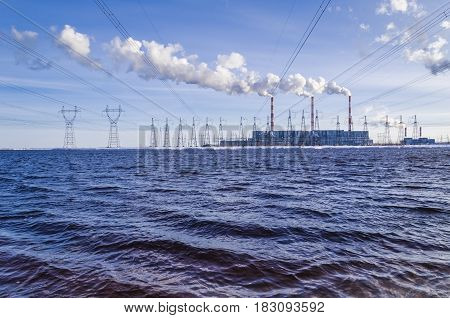 Gas power plant and power transmission towers in sunny day. Pipes with smoke. Lake foreground. Energy industry concept.