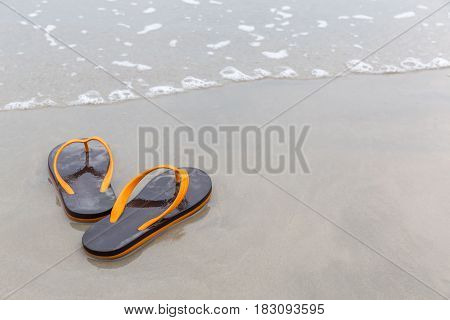 Brown and orange beach slippers on sandy ocean beach summer vacation concept.