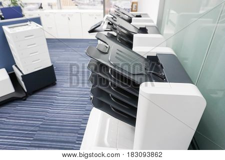 close up modern printer machine with many output feeder in office
