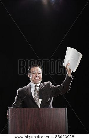 Hispanic man holding document up at podium