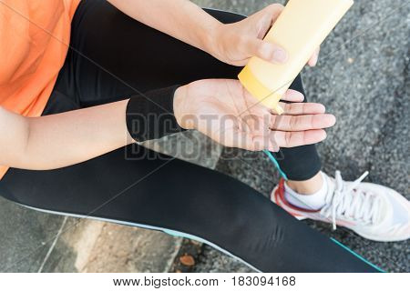 Young Asian Female Runner Sitting Down Putting Lotion On Hand And Arm