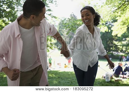 Couple running and holding hands in park