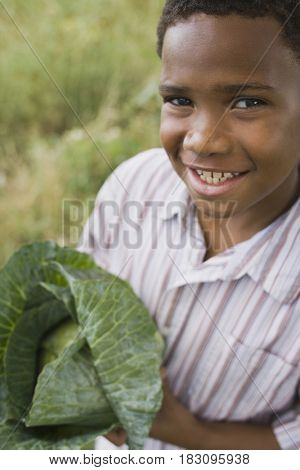 African boy holding cabbage