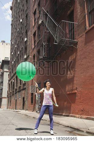 Mixed race woman holding balloon on urban street