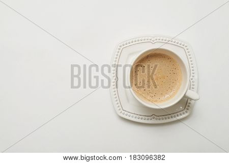 Close up of dark coffee in white porcelain cup on white background