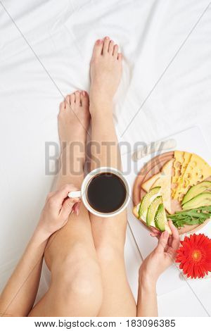 Flat lay of slim girl tasting fragrant black tea while relaxing and admiring delicious avocado