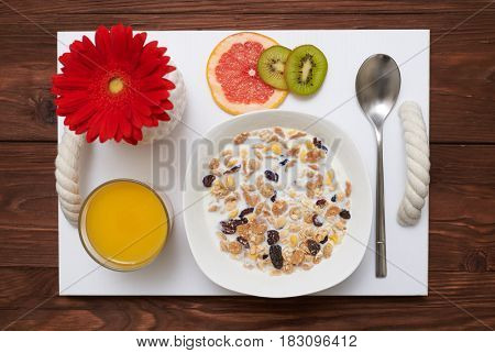 Flat lay picture of healthy breakfast in the morning. Bowl of cornflakes in milk with dried fruits
