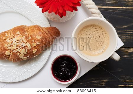 Cropped shot of french croissant sprinkled with almonds, cup of coffee and jam