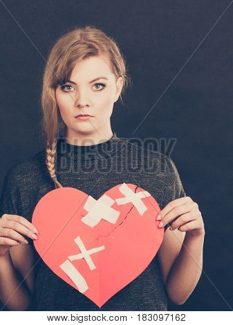 Heart broken concept. Sad unhappy blonde woman with big red love sign symbol glued by plaster. Girlfriend in valentines day. Filtered.