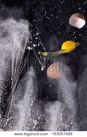 Still life - broken eggs flying between scattered flour