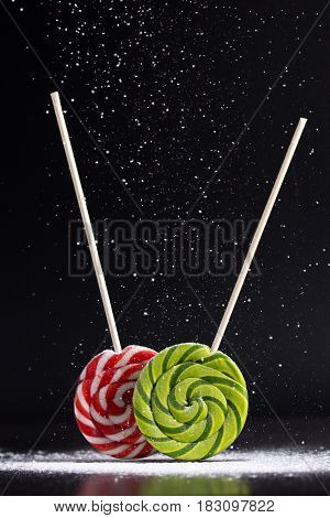Christmas still life with lollipops and powdered sugar on a black background