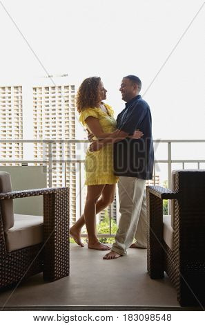 Couple hugging on urban balcony