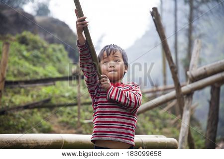 Sa Pa, Vietnam - 12 March, 2017: Ethnic minority, Hmong boy playing with the fire in tradition village of Cat cat, Sapa, Vietnam