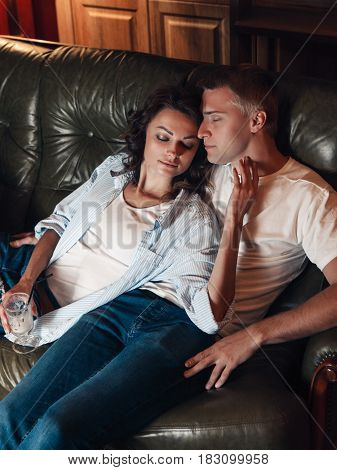 Young beautiful couple sit on couch, pleasure and rest together. Close eyes, soft touch, romantic dreams about bright future concept