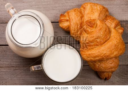 Jug and a glass of milk with a croissant on a wooden background. Top view.