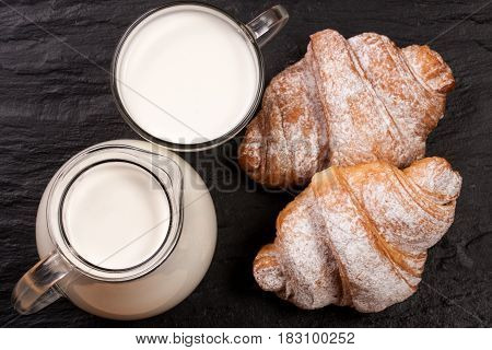 A jug and a glass of milk with two croissants on a black stone background. Top view.