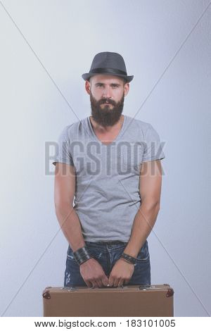 Portrait of handsome bearded man in hat standing with bag, isolated on white background