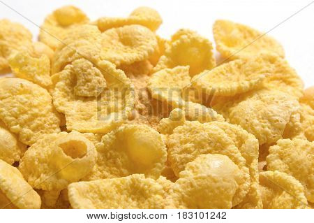 Gold corn flakes heaped on the white table.