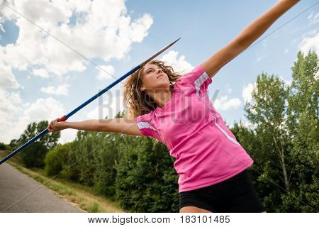 Young woman throwing a javelin during a training session outdoor in nature