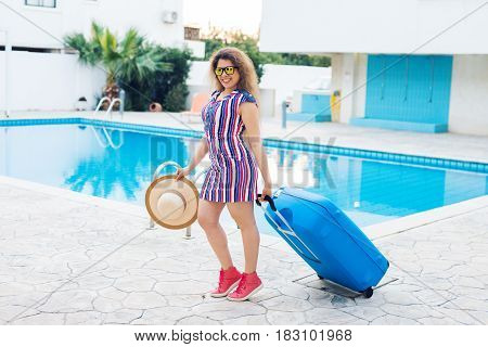 Young woman carrying blue luggage and arriving to the resort. She is walking next to the swimming pool. Beginning of summer vacation concept