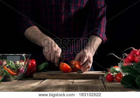 Preparing healthy food. Man cooking a salad of fresh vegetables on a wooden table
