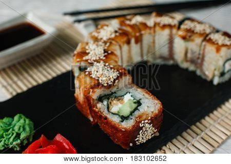 Delicious fresh sushi, uramaki golden dragon roll served on black slate, on straw mat background, closeup. Traditional Japanese food.