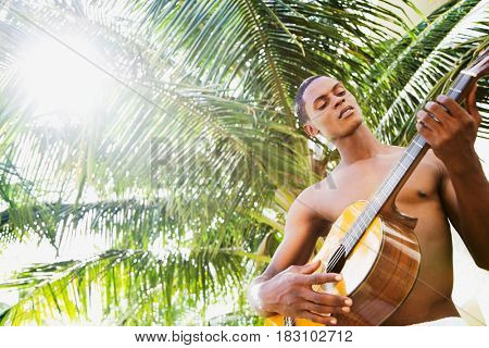 African man playing guitar in front of palm tree