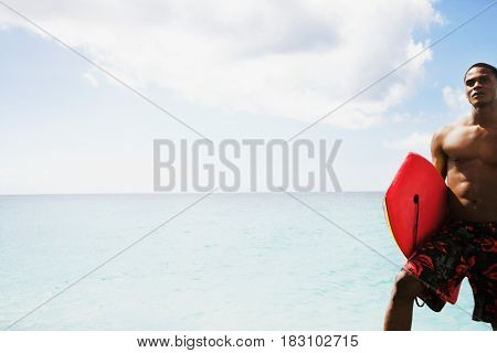 African man holding body board on beach