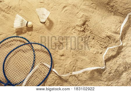 Badminton rackets net and shuttlecock on the sand top view. Summer background